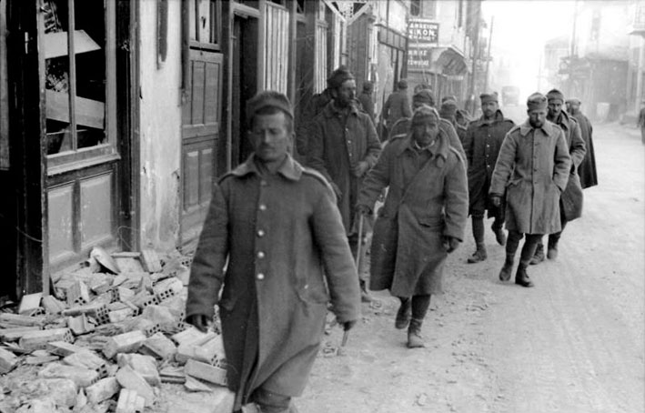 Greek soldiers march through a rubble-filled street