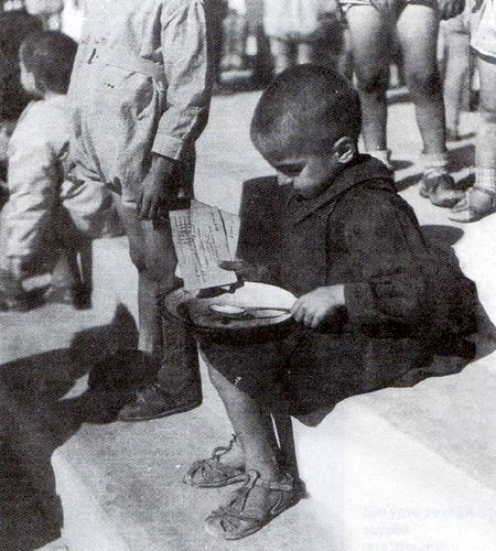 Malnourished child sitting with bowl.